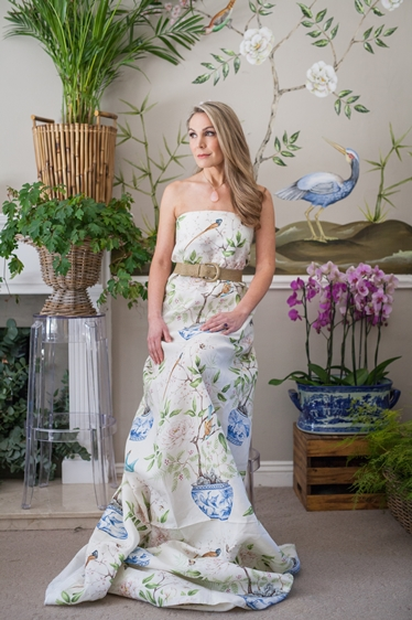 The Artist wearing Romey's Garden fabric, in front of her hand painted mural at home